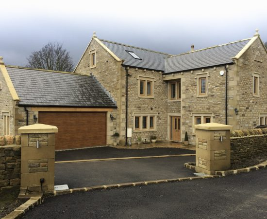 Random backing walling stone with heads cills rain guard half round copings and ashlar entrance pillars